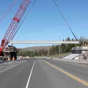 machine suspending large beam over highway