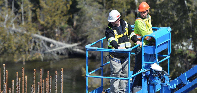 employees on lift inspecting rebar