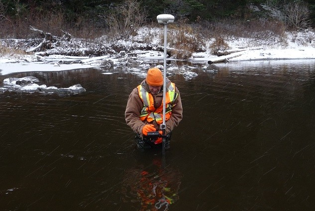 man standing in river with equipment